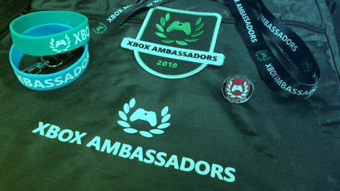 """Two bracelets, a patch, lanyard, and pin are laid on top of a bag with an """"Xbox Ambassadors"""" logo."""