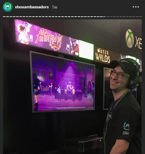 Man smiles at the camera while playing a video game.