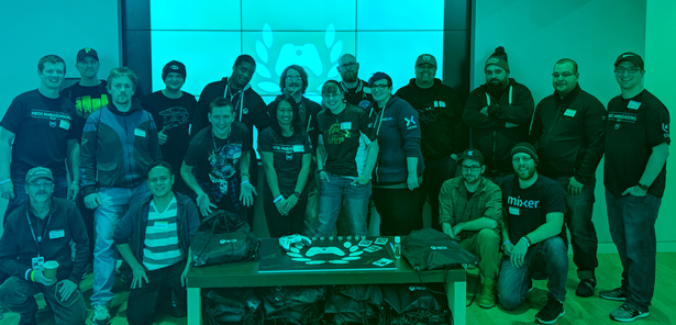 19 Xbox Ambassadors gather in front of a screen for a group photo.
