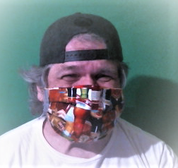 CerebralPaul, wearing a white shirt, a baseball cap, and a colorful facemask, appears to smile with his eyes